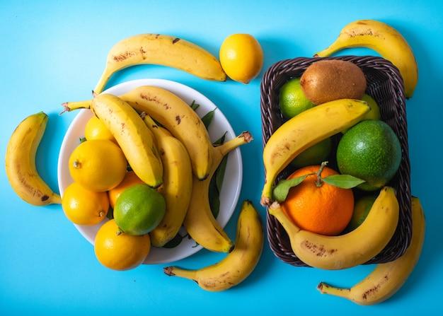 Zitrusfruchtsavocadobananen-zitronenkiwiorange in der platte und im korb auf blauer oberfläche Kostenlose Fotos