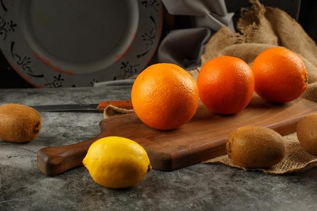 Zitrusfrüchte auf einem schneidebrett. Kostenlose Fotos