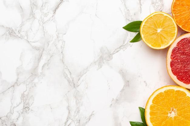 Zitrusfrüchte auf marmoroberfläche mit copyspace, frucht-flatlay, sommerliche minimalkomposition mit grapefruit, zitrone, mandarine und orange Premium Fotos