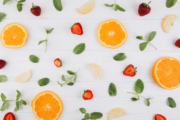 Zitrusfrüchte, blätter und erdbeeren auf dem blauen holztisch. Premium Fotos