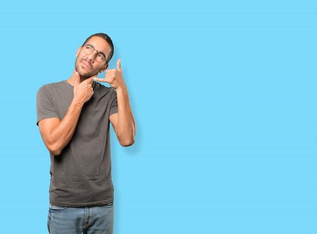 Zögerlich junger mann mit einer geste des aufrufs mit der hand machen Premium Fotos