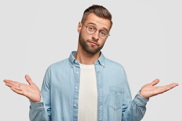 Zögernder verwirrter unrasierter mann zuckt verwirrt mit den schultern, fühlt sich unentschlossen, hat borsten, einen trendigen haarschnitt, ist in ein blaues, stilvolles hemd gekleidet und auf einer weißen wand isoliert. ahnungsloser mann posiert drinnen Kostenlose Fotos