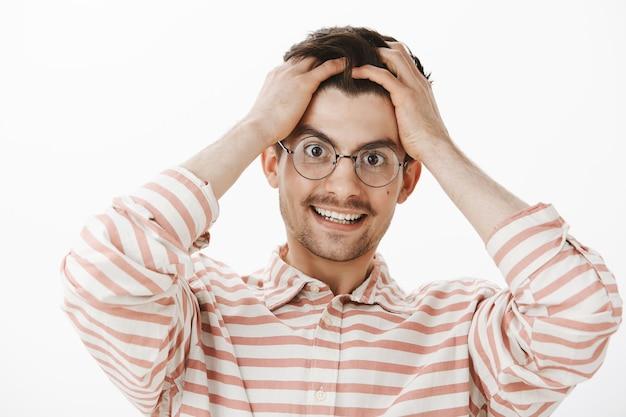 Zu viele gedanken in einem gehirn. unter druck stehender freundlicher kaukasischer mann mit bart und schnurrbart in brille, hände auf dem kopf haltend und fröhlich lächelnd, versuchend, während der arbeit erschöpft positiv zu bleiben Kostenlose Fotos