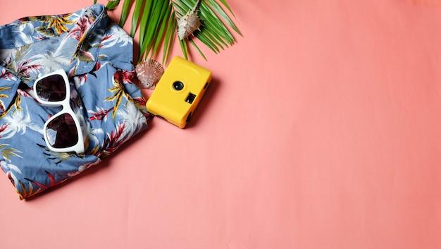 Zubehörreisendkamerahemden und sonnenbrillepalmblatt auf rosa hintergrund und copyspace. draufsichtkonzept sommer. Premium Fotos