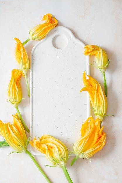 Zucchiniblumen auf einem weißen brett Premium Fotos