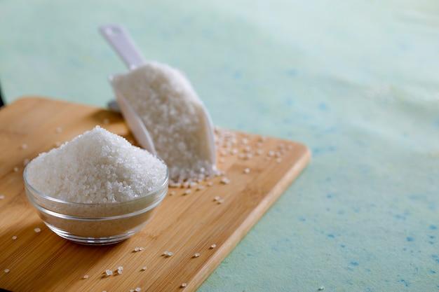 Zucker in der glasschüssel auf hölzernem hintergrund Premium Fotos