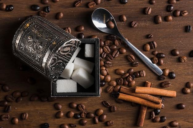 Zuckerdose in der nähe von zimtstangen, löffel und kaffeebohnen Kostenlose Fotos