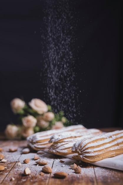 Zuckerpulver, das auf dem gebackenen eclair mit mandeln gegen schwarzen hintergrund abwischt Kostenlose Fotos