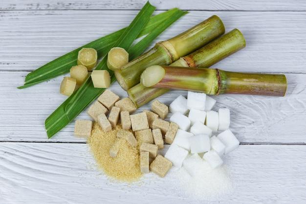 Zuckerrohr mit den braunen und würfeln des raffinierten zuckers auf hölzernem hintergrund Premium Fotos