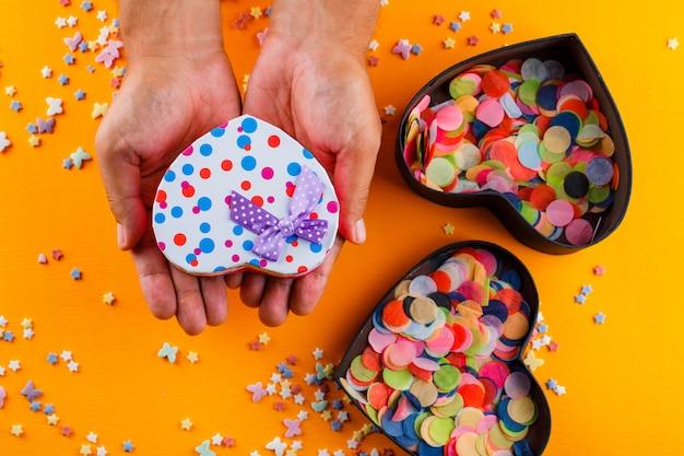 Zuckerstreusel, konfetti in kisten auf gelbem tisch und männchen mit geschenkbox. Kostenlose Fotos