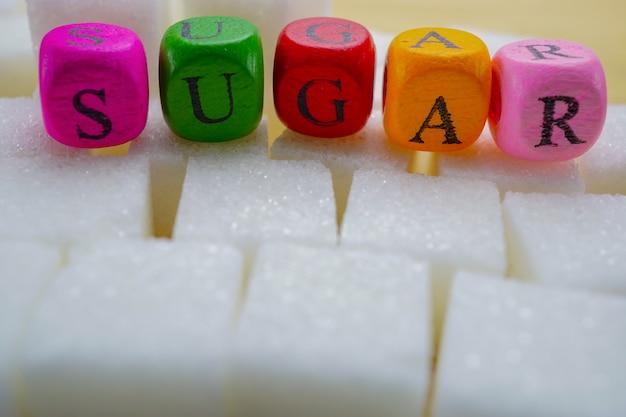 Zuckersüße würfel mit bunten hohen kalorien des englischen alphabetes: gesunder nahrungsmittelbetrug der fetten diät Premium Fotos