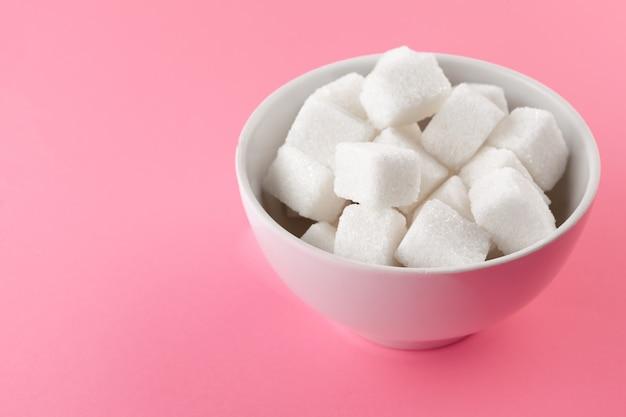 Zuckerwürfel in einer schüssel auf rosa hintergrund Premium Fotos