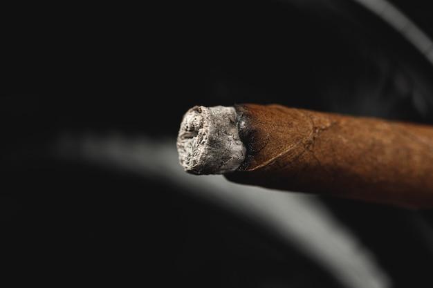Zünde eine zigarre in einem aschenbecher an. Premium Fotos