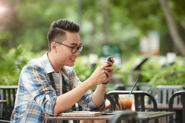 Zufällig gekleideter junger asiatischer mann, der café am im freien sitzt und smartphone verwendet Kostenlose Fotos