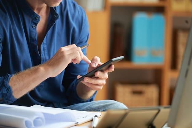 Zufällig gekleideter nicht erkennbarer mann, der smartphone bei der arbeit im büro verwendet Kostenlose Fotos