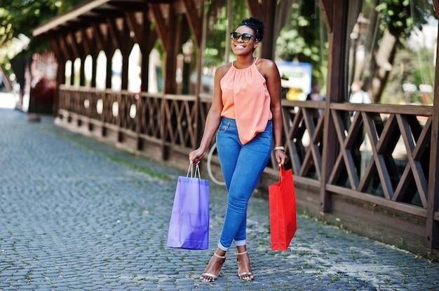 Zufälliges afroamerikanermädchen mit dem farbigen einkaufstaschegehen im freien. stilvolles einkaufen der schwarzen frau. Premium Fotos
