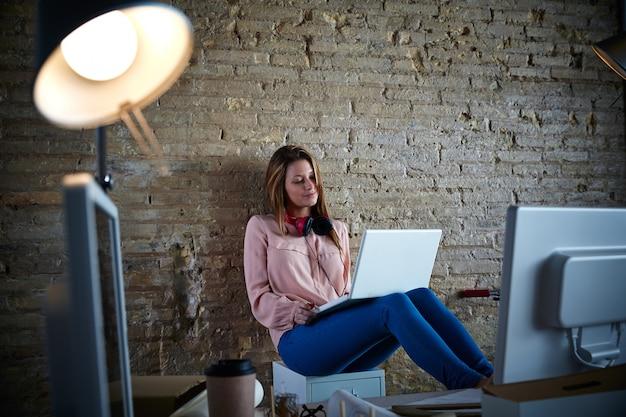 Zufälliges sitzen der geschäftsfrau im büro mit laptop Premium Fotos