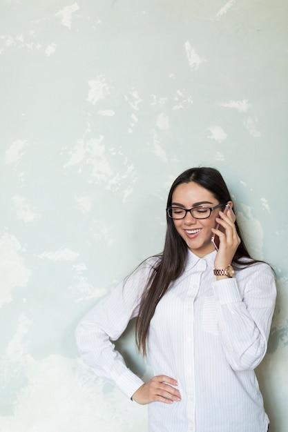 Zufriedene frau, die am telefon spricht Kostenlose Fotos