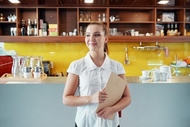 Zufriedene frau mit dem klemmbrett, das kaffeestubegeschäft handhabt Kostenlose Fotos