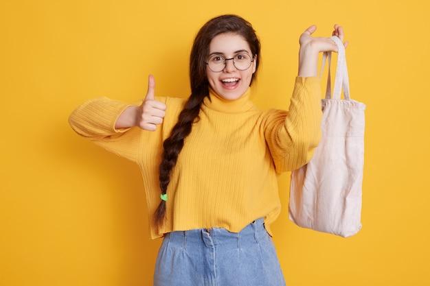 Zufriedene frau mit langem zopf zeigt daumen hoch und hält tasche in der hand, genießt ihren einkauf Kostenlose Fotos