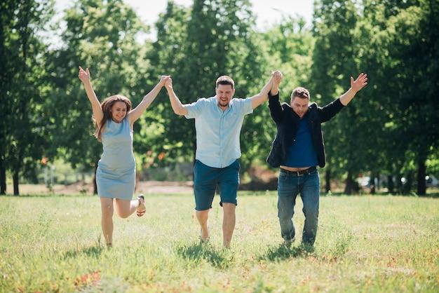Zufriedene freunde, die hände hochlaufen und halten Kostenlose Fotos