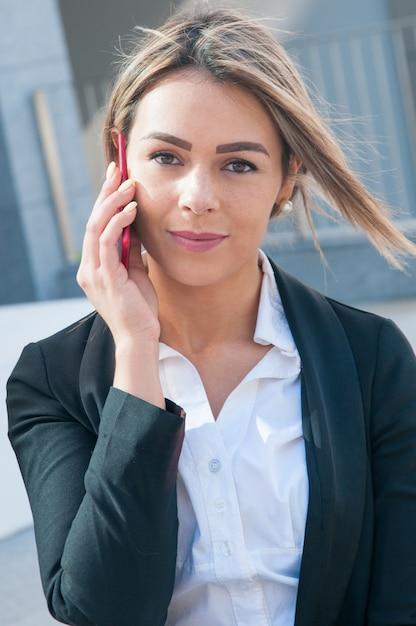 Zufriedene geschäftsfrau, die draußen auf smartphone spricht Kostenlose Fotos