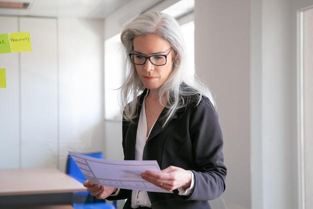 Zufriedene geschäftsfrau in brillen, die statistiken lesen. erfolgreicher konzentrierter grauhaariger arbeitgeber im anzug, der im büroraum steht und dokument hält. marketing-, geschäfts- und managementkonzept Kostenlose Fotos