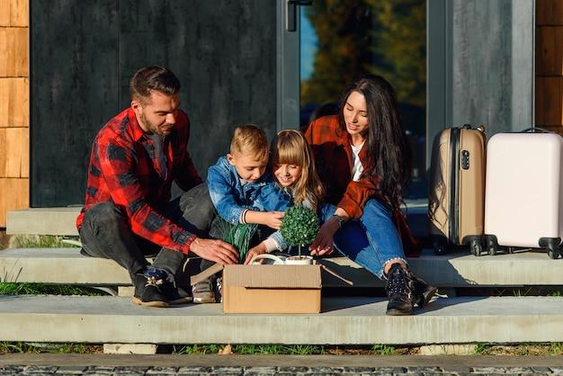 Zufriedene junge eltern mit ihren glücklichen kindern sitzen auf der treppe des neuen hauses und holen aus dem karton grüne blumentöpfe und uhr. neues stilvolles gemütliches haus der schönen familie nahe wald. Premium Fotos