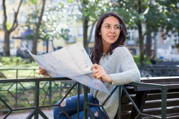 Zufriedene junge frau, die draußen papierkarte auf bank verwendet Kostenlose Fotos