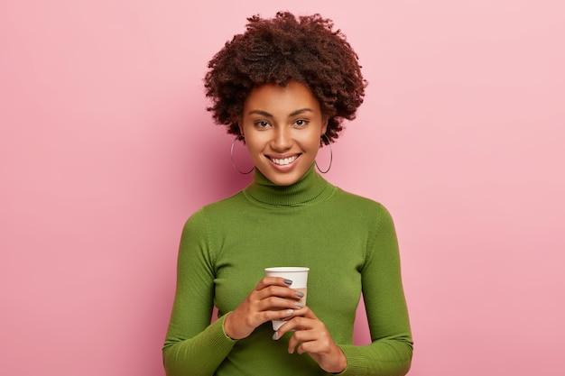 Zufriedene lockige frau genießt kaffeepause, hält einwegbecher getränk, sieht glücklich aus, trägt grünen rollkragenpullover, lächelt freudig, hat freizeit nach der arbeit isoliert an rosa wand Kostenlose Fotos