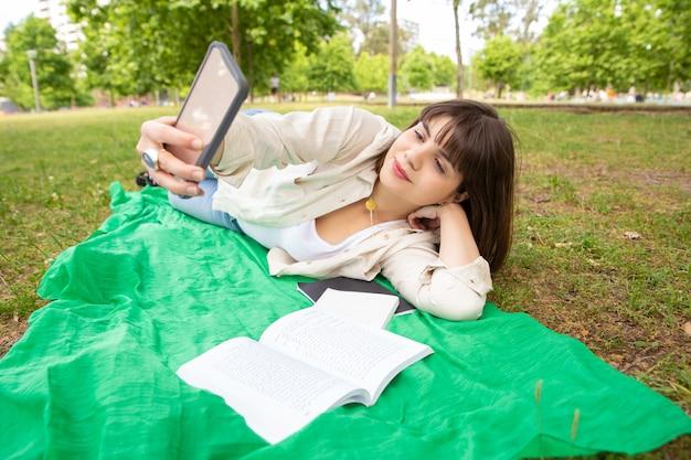 Zufriedene weibliche frau, die smartphone im park verwendet Kostenlose Fotos