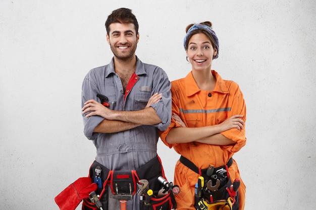 Zufriedene weibliche und männliche techniker in spezieller uniform halten die hände gefaltet, während sie auf anweisungen des arbeitsaufsehers oder vorarbeiters warten Kostenlose Fotos