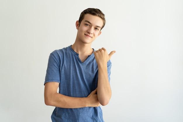 Zufriedener hübscher junger mann im blauen t-shirt beiseite zeigend Kostenlose Fotos