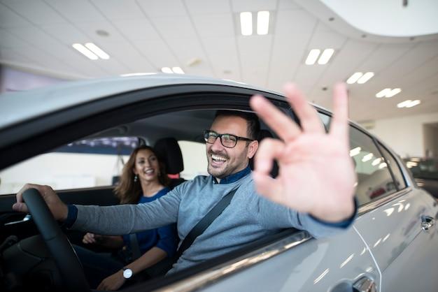 Zufriedener kunde, der neues auto im autohaus kauft Kostenlose Fotos