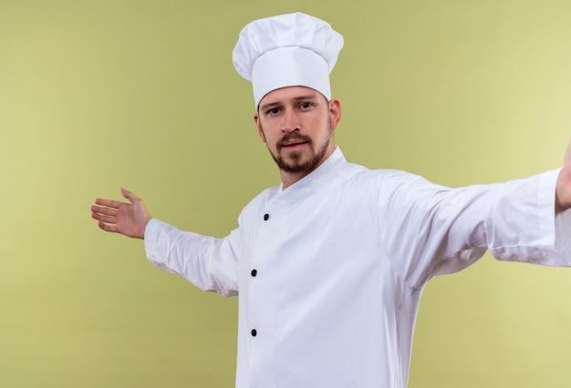 Zufriedener professioneller männlicher koch kocht in der weißen uniform und im kochhut, der zuversichtlich schaut, begrüßungsgeste mit den händen zu machen, die über grünem hintergrund stehen Kostenlose Fotos