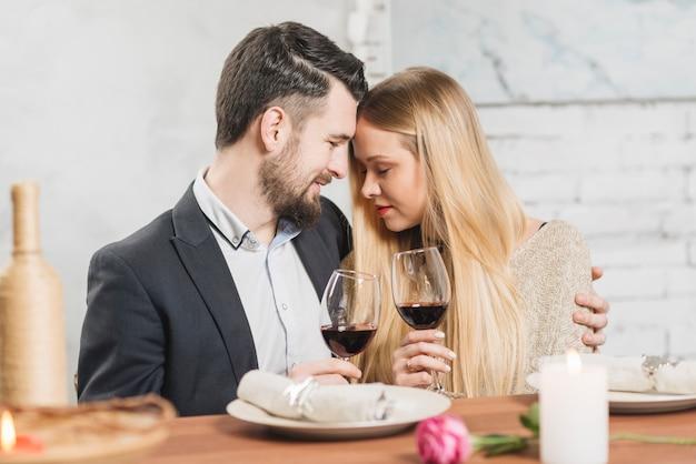 Zufriedenes paar verliebt in weingläser Kostenlose Fotos
