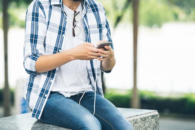 Zugeschnittener mann, der auf marmortreppen sitzt und die musik von der app einschaltet Kostenlose Fotos