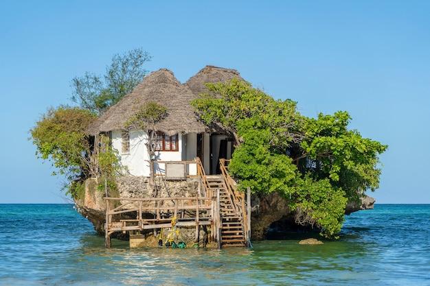 Zuhause auf dem felsen bei flut im meerwasser auf der insel sansibar Premium Fotos
