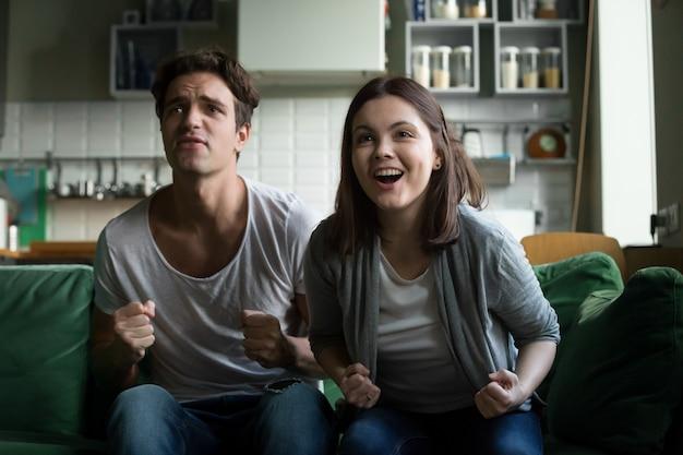 Zujubelndes unterstützendes gewinnendes team der paare, das zu hause fernsehspiel überwacht Kostenlose Fotos