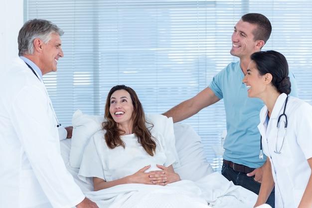 Zukünftige eltern, die mit lächelnden doktoren sprechen Premium Fotos