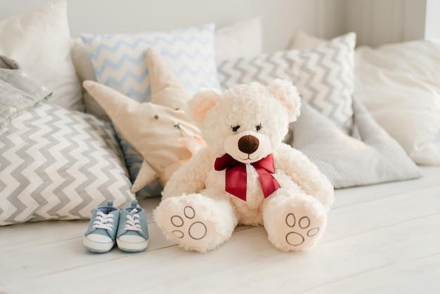 Zukünftiges baby des weichen spielzeugbären und der blauen turnschuhe auf dem bett in den kissen Premium Fotos