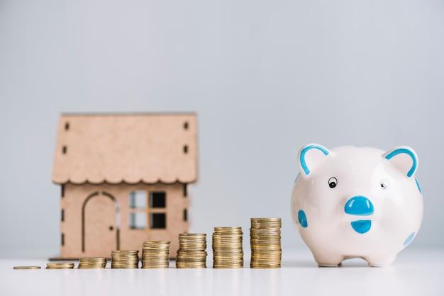 Zunehmende gestapelte münzen; sparschwein und hausmodell auf weißem reflektierendem schreibtisch Kostenlose Fotos