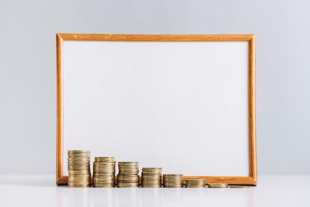 Zunehmende staplungsmünzen vor leerem weißem brett auf reflektierendem schreibtisch Kostenlose Fotos