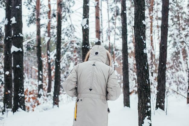 Zurück des mannes im wintermantel gehen in schneewald Kostenlose Fotos
