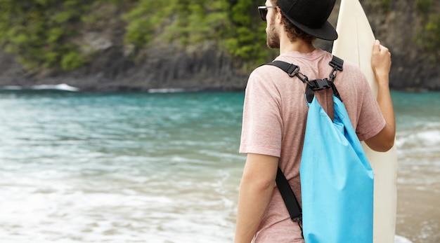 Zurück geschossen von kaukasischem mann mit blauer tasche, die surfbrett hält, seine freunde beim surfen beobachtet, riesenwellen an windigem sommertag reitend Kostenlose Fotos