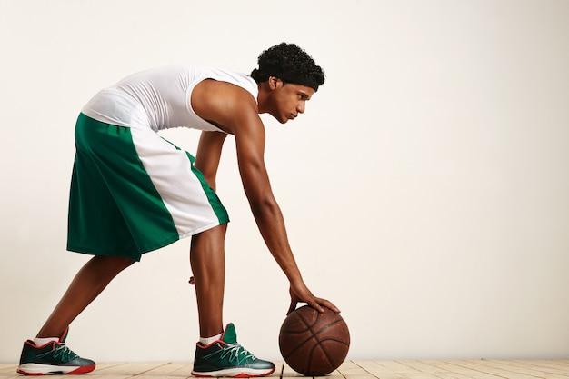Zurück geschossenes foto des basketballspielers, der den ball an seiner seite auf weiß hält Kostenlose Fotos