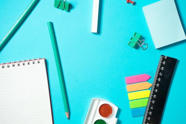 Zurück in die schule verspotten. flache komposition mit aquarell, bleistift, notizbuch, lineal, radiergummi. isometrisches konzept auf blauem hintergrund. pop-art. schulmaterial. overhead. branding mock-up-briefpapier Premium Fotos