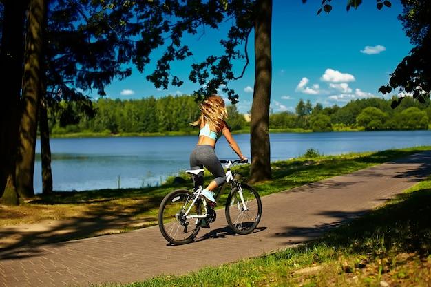 Zurück vom vorbildlichen fahren der blonden frau der sexy heißen sportfrau auf fahrrad im grünen sommerpark nahe see mit dem fliegen des erhöhten haares in einer luft Kostenlose Fotos