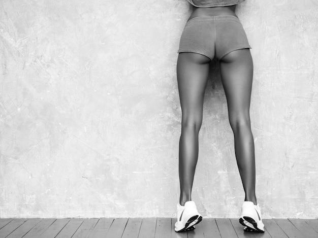 Zurück von der eignungsfrau in der sportkleidung, die überzeugt schaut junge weibliche tragende sportkleidung. schönes modell mit perfektem gebräuntem körper frau, die im studio nahe grauer wand aufwirft Kostenlose Fotos
