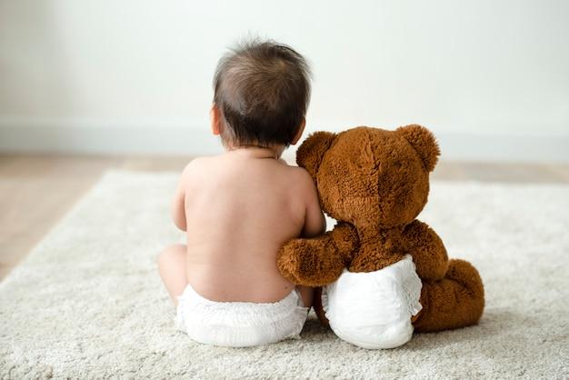 Zurück von einem baby mit einem teddybären Premium Fotos